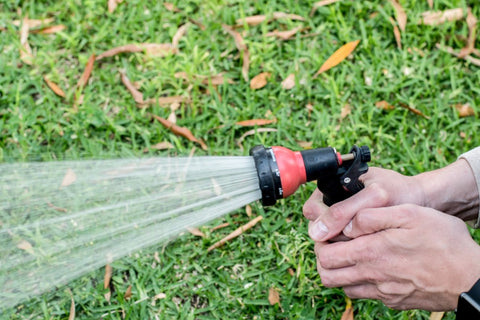 Someone watering grass with a hose.