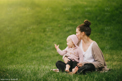 Adult and child sitting in grass