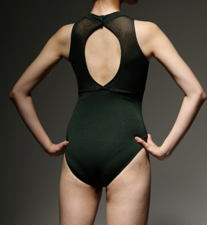 back of woman wearing dark green sheer front ballet leotard with open back