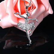 front of crystal ballerina pendant necklace in front of a rose