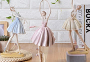 front of three ballet dancer figurines wearing different colored skirts