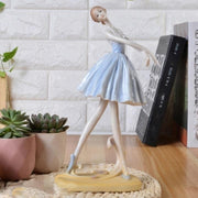 front of ballet dancer figurine wearing blue skirt