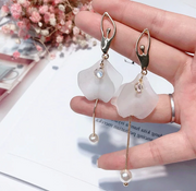 front of gold tone and white ballerina dangle earrings