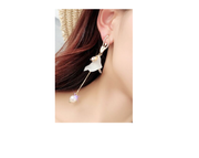 woman wearing gold tone and white ballerina dangle earrings
