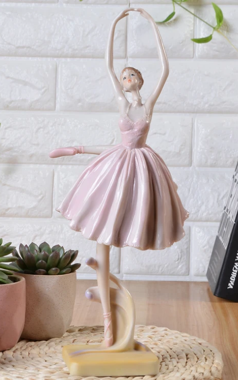 front of ballet dancer figurine wearing pink skirt