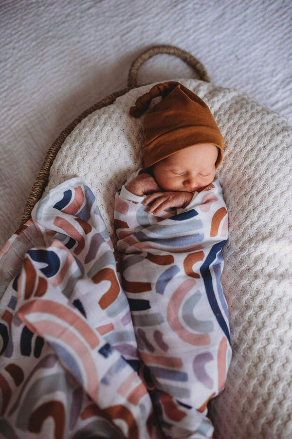 baby wrapped in rainbow baby organic swaddle