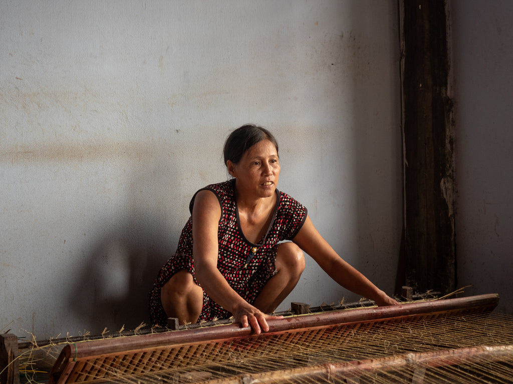 Vietnamese woman weaving a sleeping mat