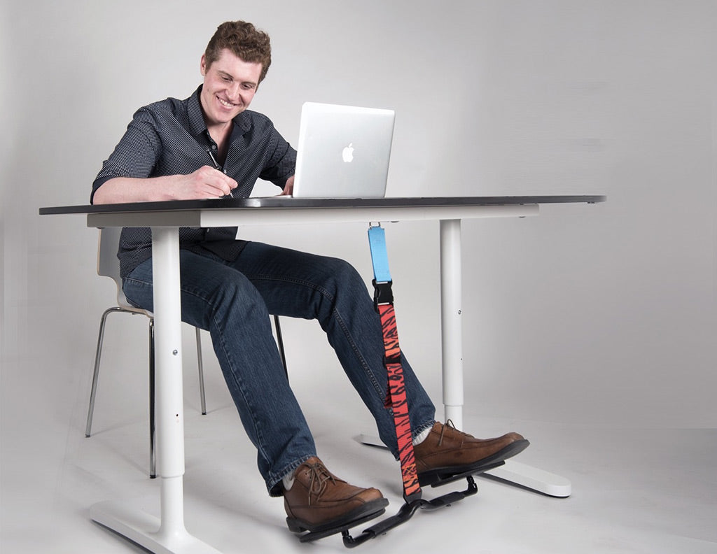 man using desk exercise tool at work to increase daily physical activity