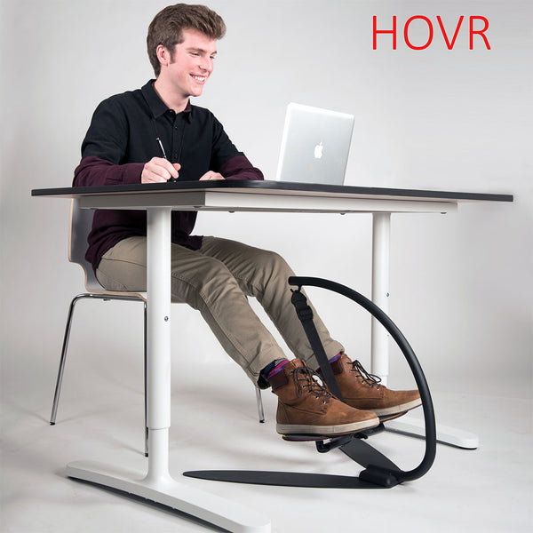 man sitting at desk using hovr desk exercise equipment