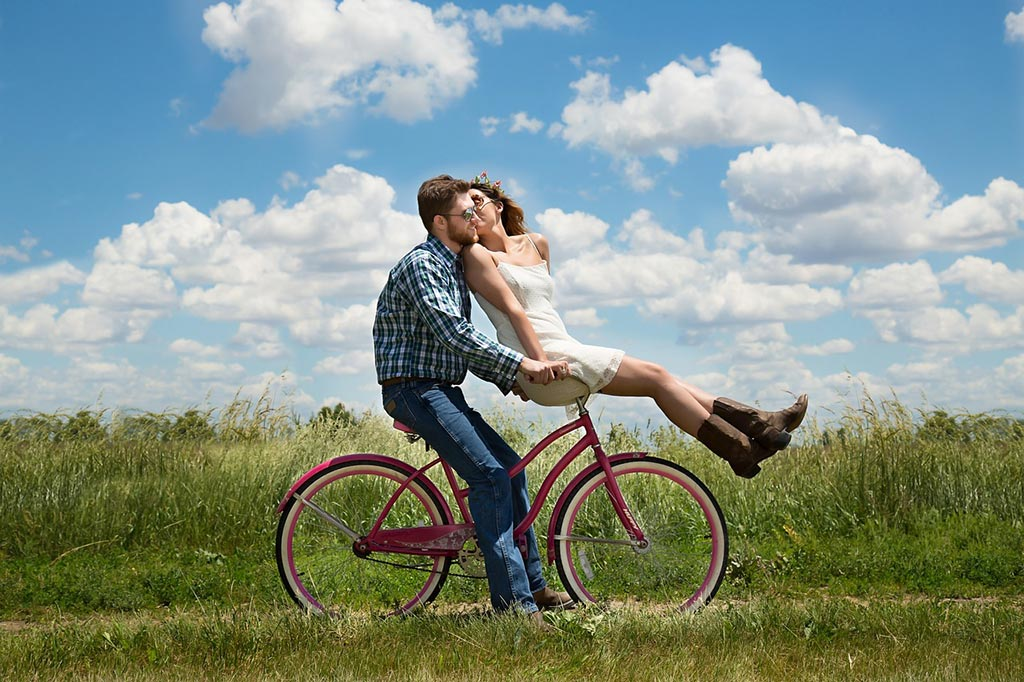 couple riding a bike in the fields to increase daily physical activity