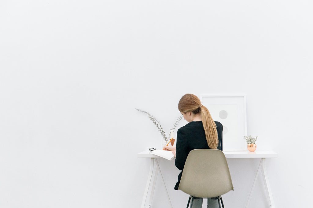 Female desk employee sitting in an all white office