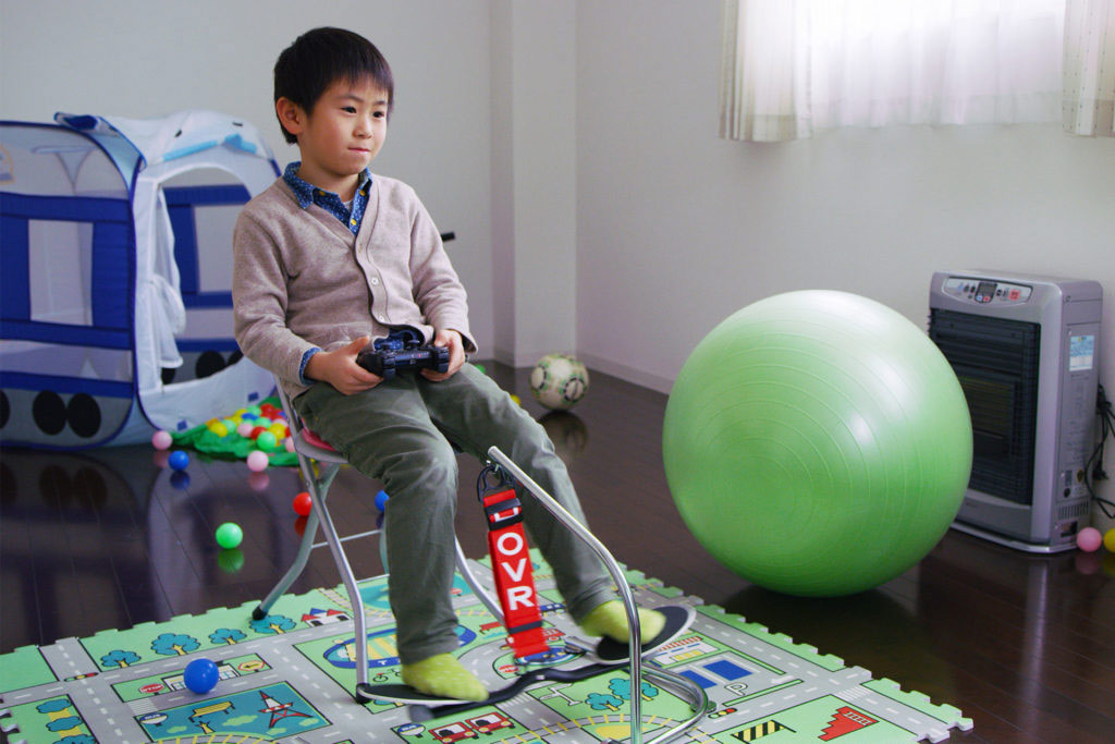 young boy using hovr portable leg swing while playing video games