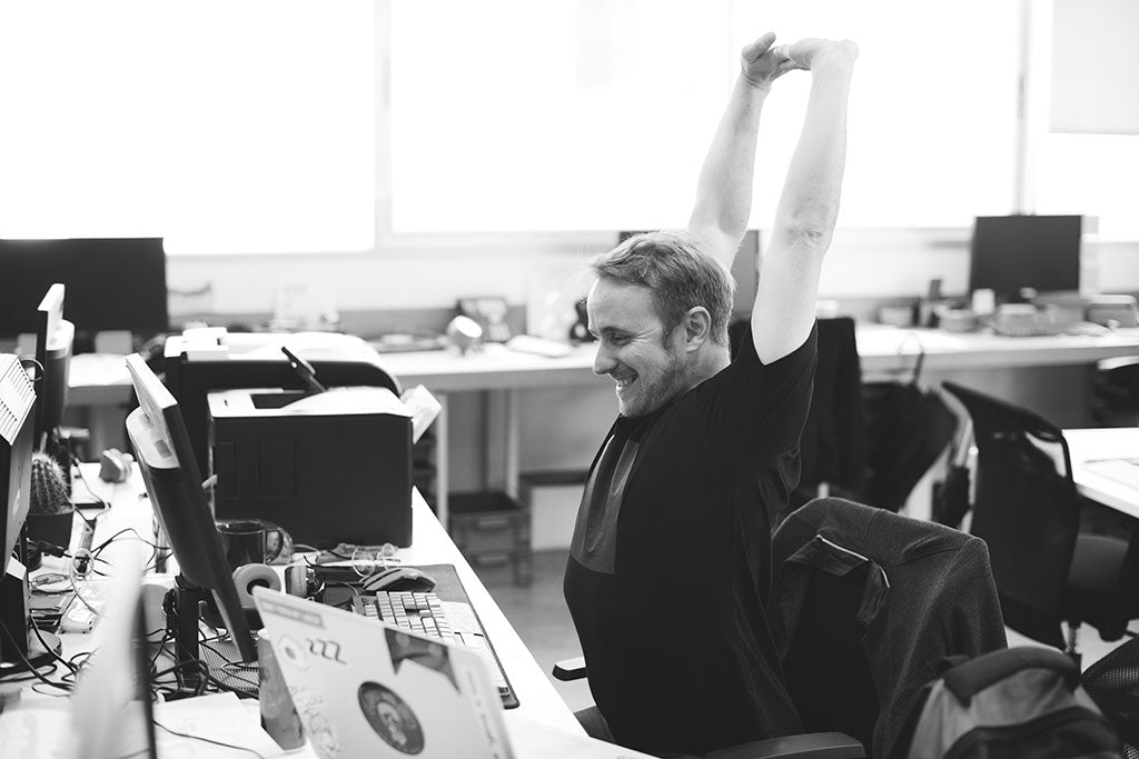 man doing stretches and exercising at his desk at work
