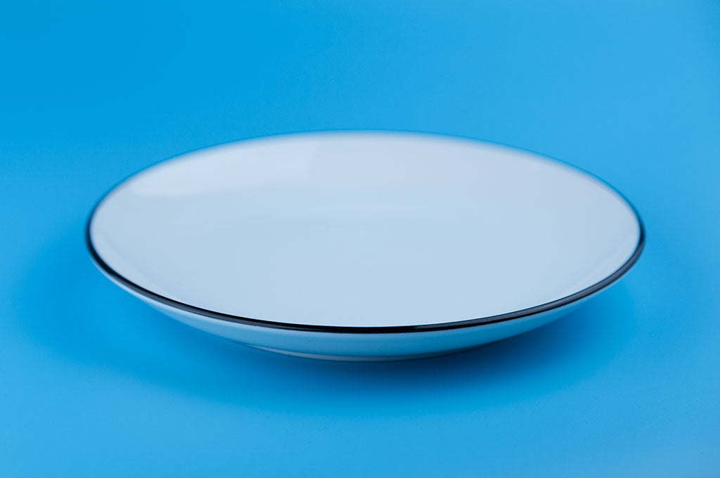 empty white plate against blue background