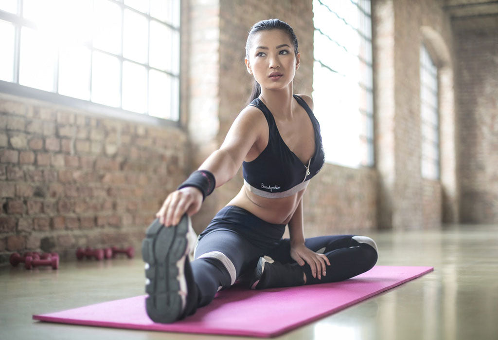 woman stretching her legs on a yoga mat