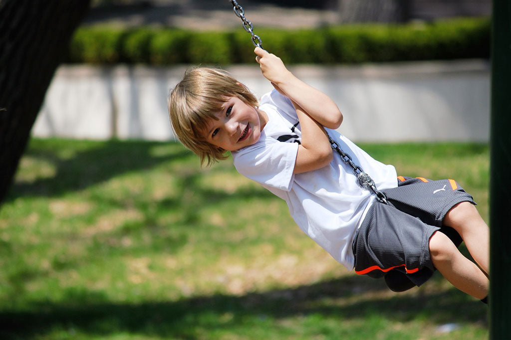 blonde child playing on the swing