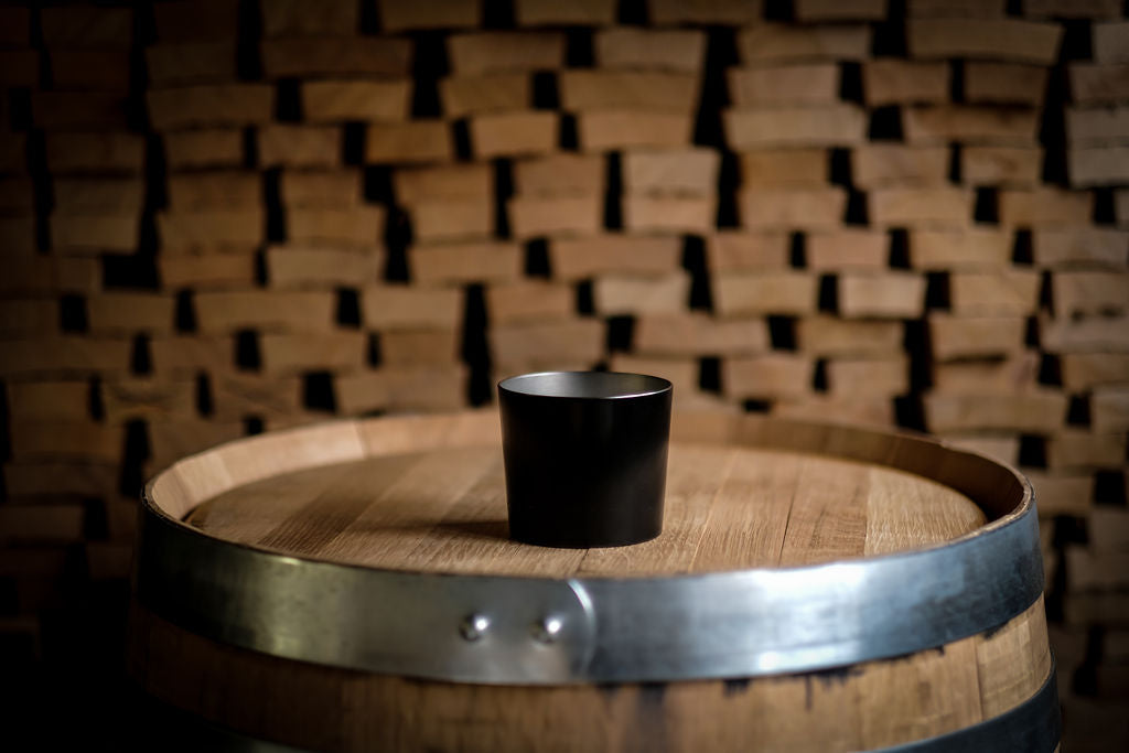 THE DOM original tin cup whiskey glass tumbler on top of a bourbon barrel with stacked wood in the background