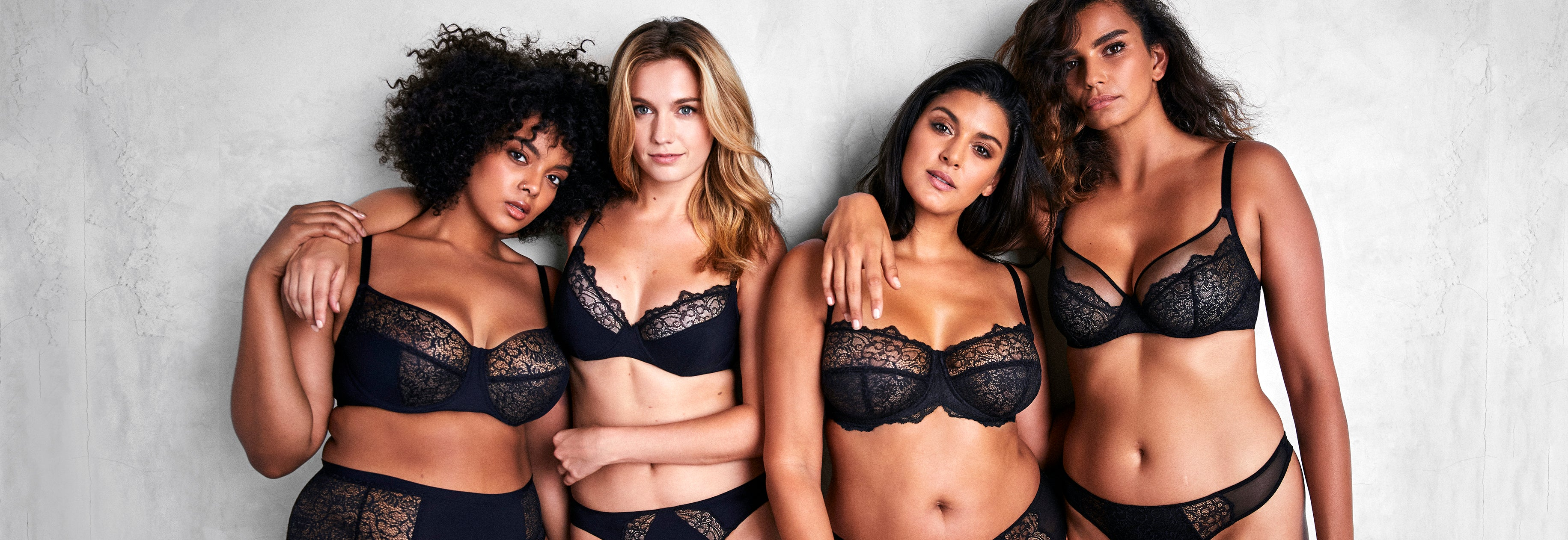 Liberté campaign photo of four models wearing Liberté lingerie. From left to right the models are wearing the Crosby Demi Bra with Crosby High Rise Brief, the Crosby Plunge Bra with Crosby Scalloped Cheeky, Bowery Lace Demi Bra with Bowery Scalloped Hipster and Bowery Mesh Plunge Bra with Bowery Mesh Thong.