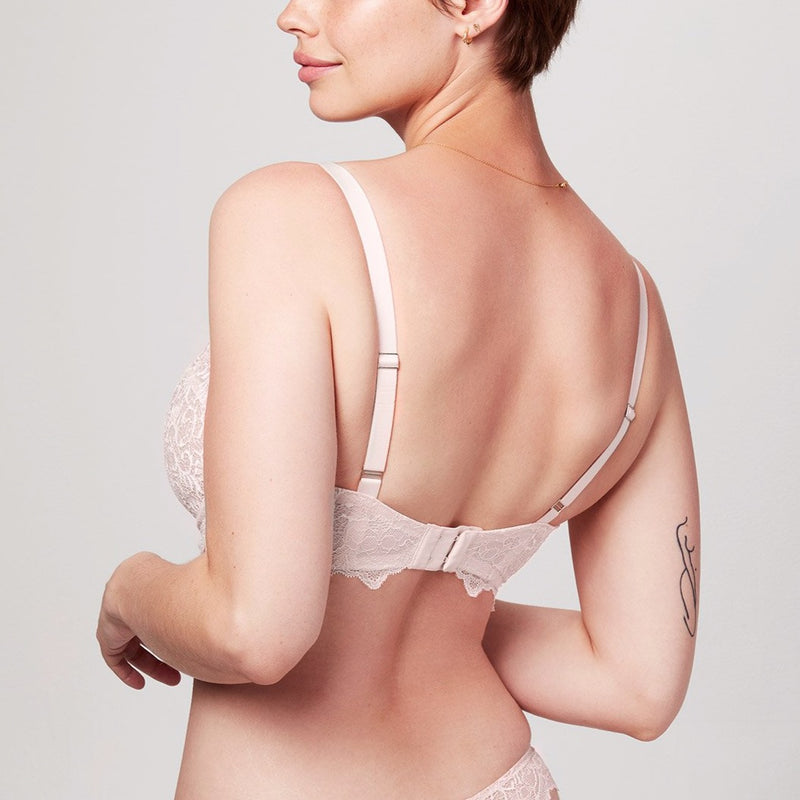 Back view of curve model wearing a blush pink Liberté Bowery Lace Demi Bra with scalloped edges on the band