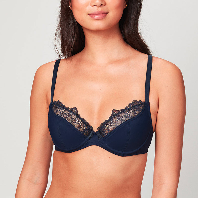 Model wearing a midnight blue Liberté Crosby Plunge Bra with Crosby performance micro jersey on the bottom cup and lace with scalloped edges on the top cup.