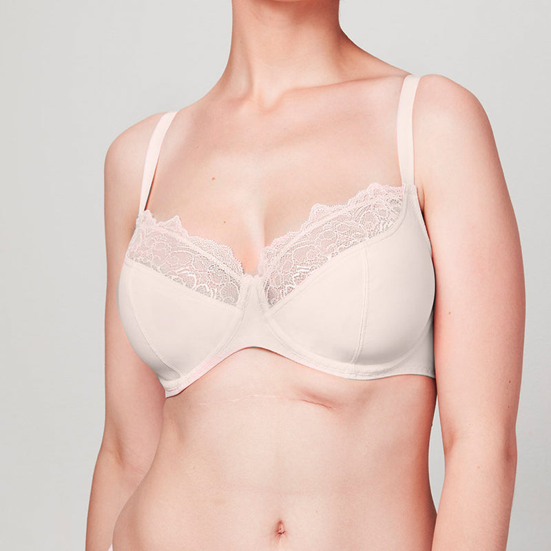 Model wearing a blush pink Liberté Crosby Plunge Bra with Crosby performance micro jersey on the bottom cup and lace with scalloped edges on the top cup.