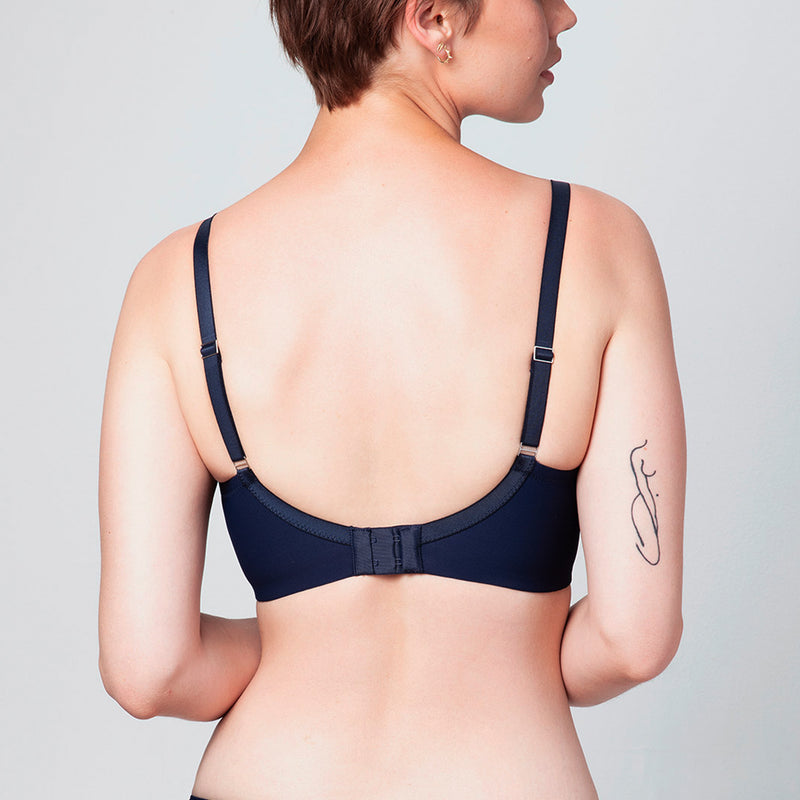Back view of curve model wearing a midnight blue Liberté Crosby Demi Bra featuring a Crosby performance micro jersey band.