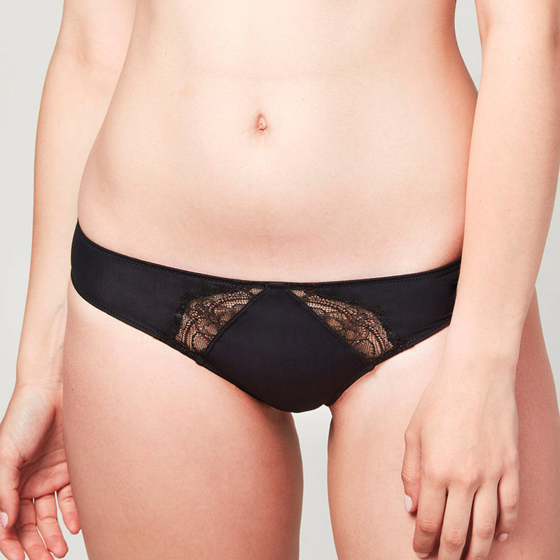 Model wearing a Liberté Crosby Scalloped Cheeky in black, featuring Crosby performance micro jersey and lace insets.
