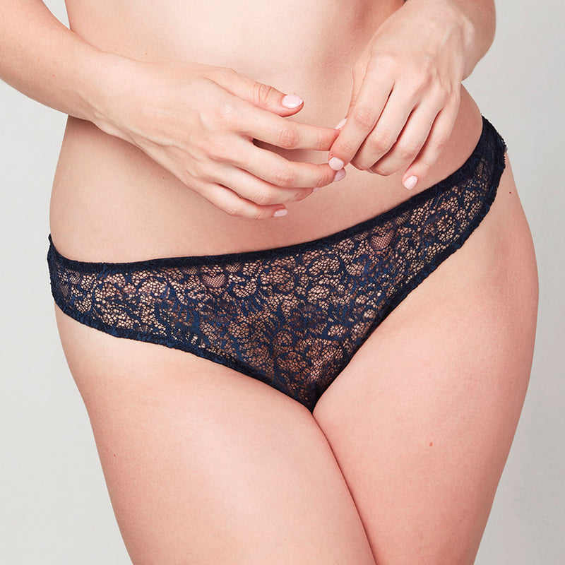Model wearing a Liberté Bowery Scalloped Thong, with a sheer all lace front in Midnight Blue.