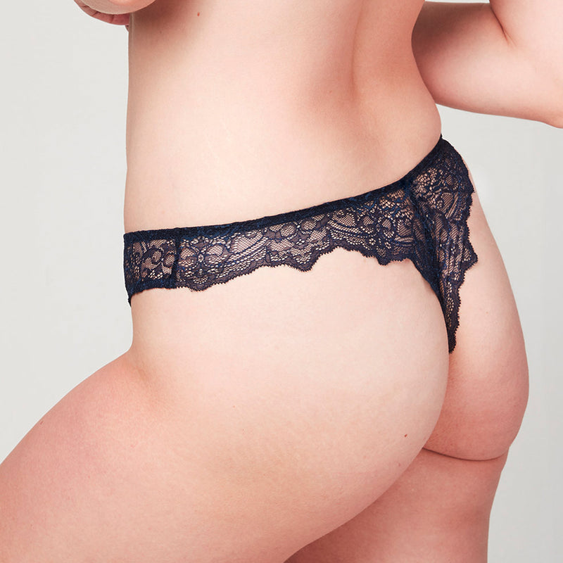 Back view of model wearing a Liberté Bowery Scalloped Thong featuring a sheer lace with scalloped edges in Midnight Blue.