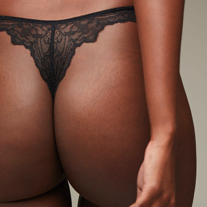 Back view of model wearing a Liberté Bowery Scalloped Thong featuring a sheer lace with scalloped edges in black.