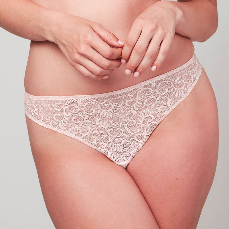 Model wearing a Liberté Bowery Scalloped Thong, with a sheer all lace front in blush pink.