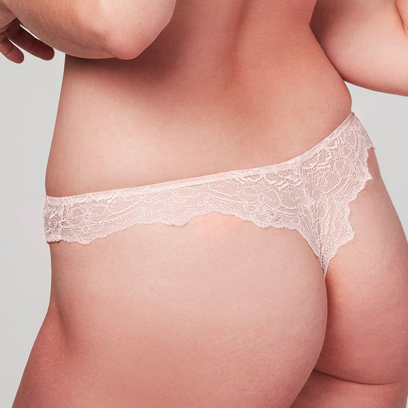 Back view of model wearing a Liberté Bowery Scalloped Thong featuring a sheer lace with scalloped edges in blush pink.