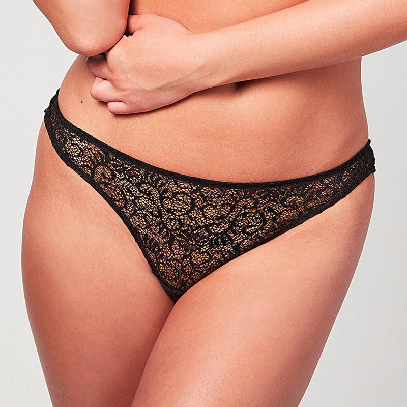 Model wearing a Liberté Bowery Scalloped Thong, with a sheer all lace front in black.