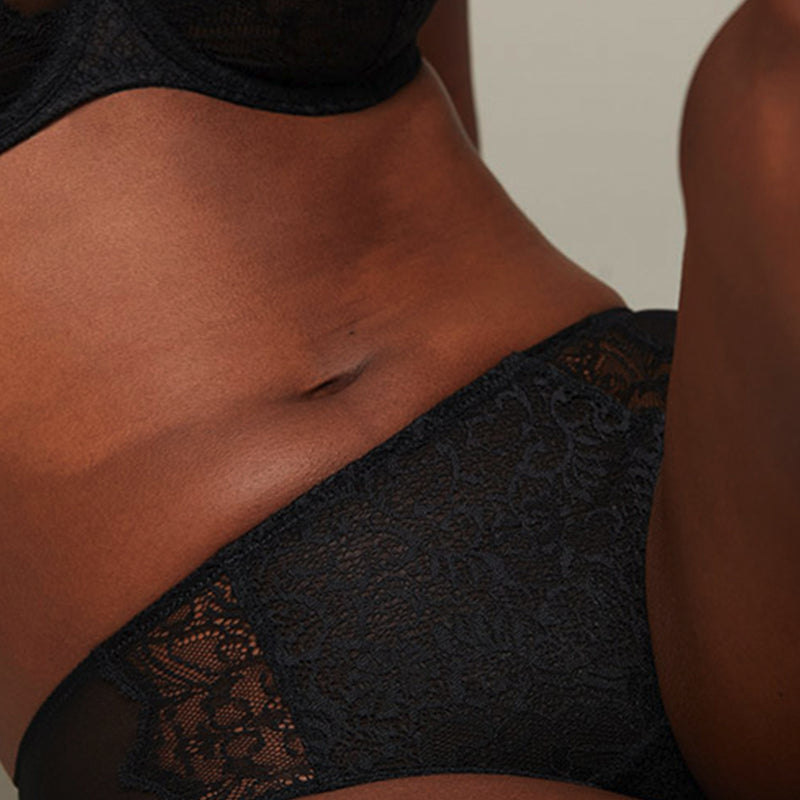 Close up of model wearing a Liberté Bowery Scalloped Hipster, with a semi sheer lace front and sheer mesh sides in black.