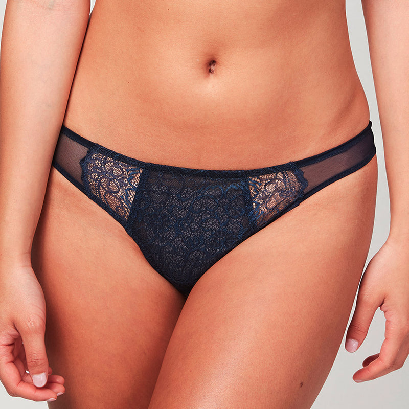 Model wearing a Liberté Bowery Mesh Thong, with a semi sheer lace front and mesh sides in midnight blue