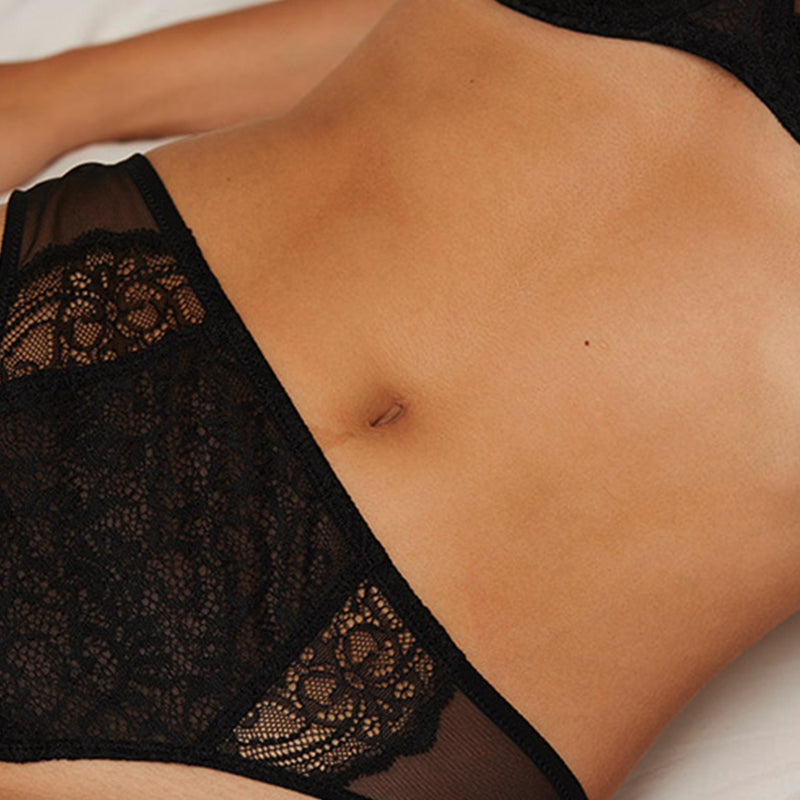 Close up of model wearing a Liberté Bowery Mesh Thong, with a semi sheer lace front and mesh sides in onyx black