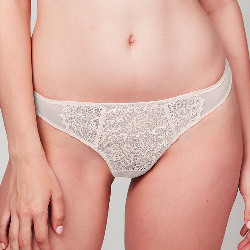 Model wearing a Liberté Bowery Mesh Thong, with a semi sheer lace front and mesh sides in blush pink Edit alt text