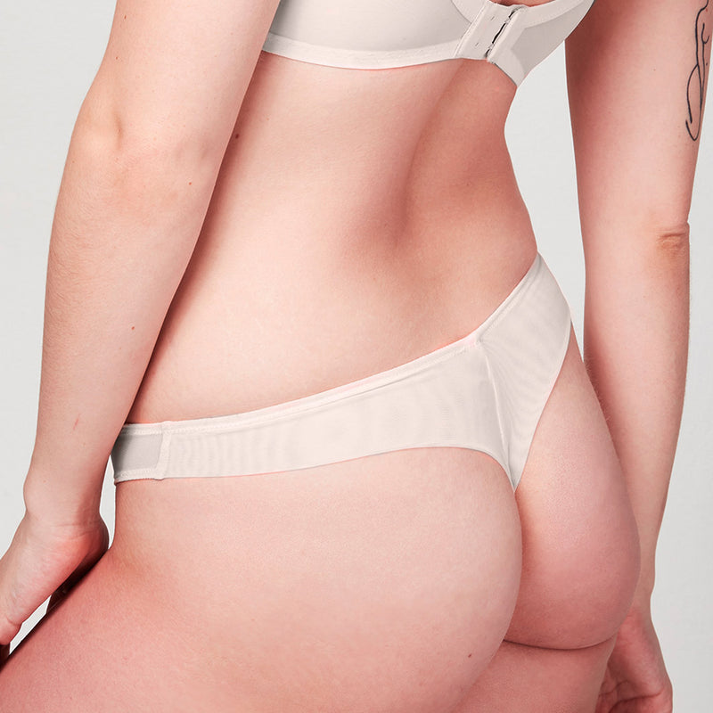 Back view of model wearing a Liberté Bowery Mesh Thong, with a semi sheer mesh back in blush pink