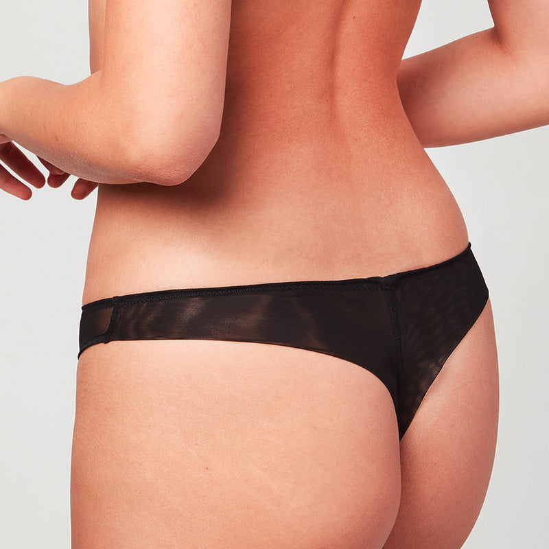 Back view of model wearing a Liberté Bowery Mesh Thong, with a semi sheer mesh back in onyx black