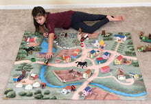 A girl plays on the Jumbo sized Caravan Village ImaginOak children's play mat with the toys she already has.