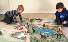 Two boys play with figurines on the Horse Haven children play mat.
