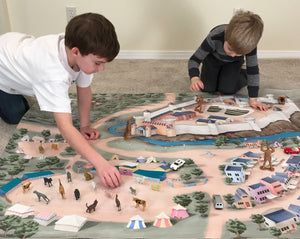 Two boys play with figurines on the Quest Realm medieval castle play mat.