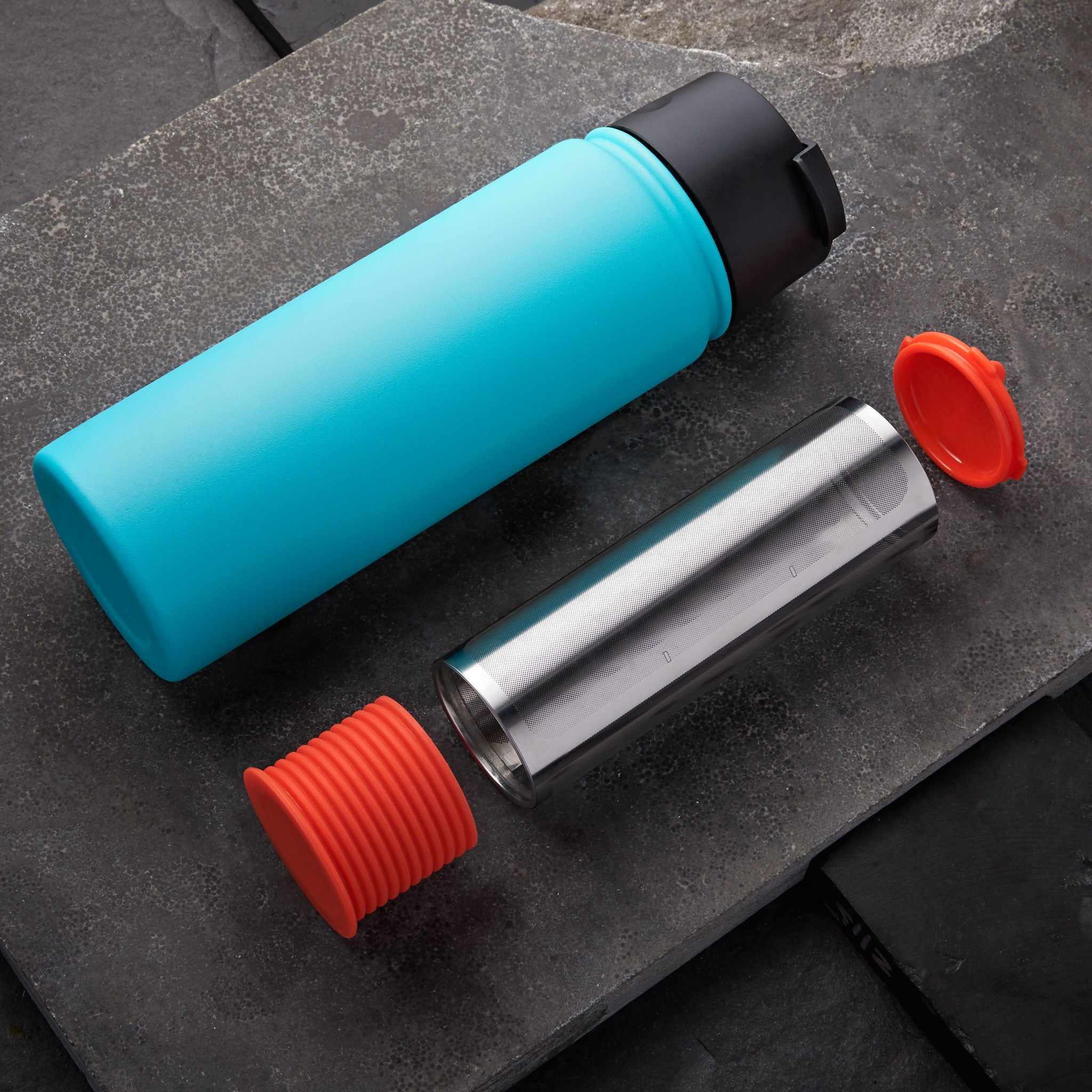 Rumble Go cold brew coffee filter with orangey-red cap and base next to one of many compatible water bottles