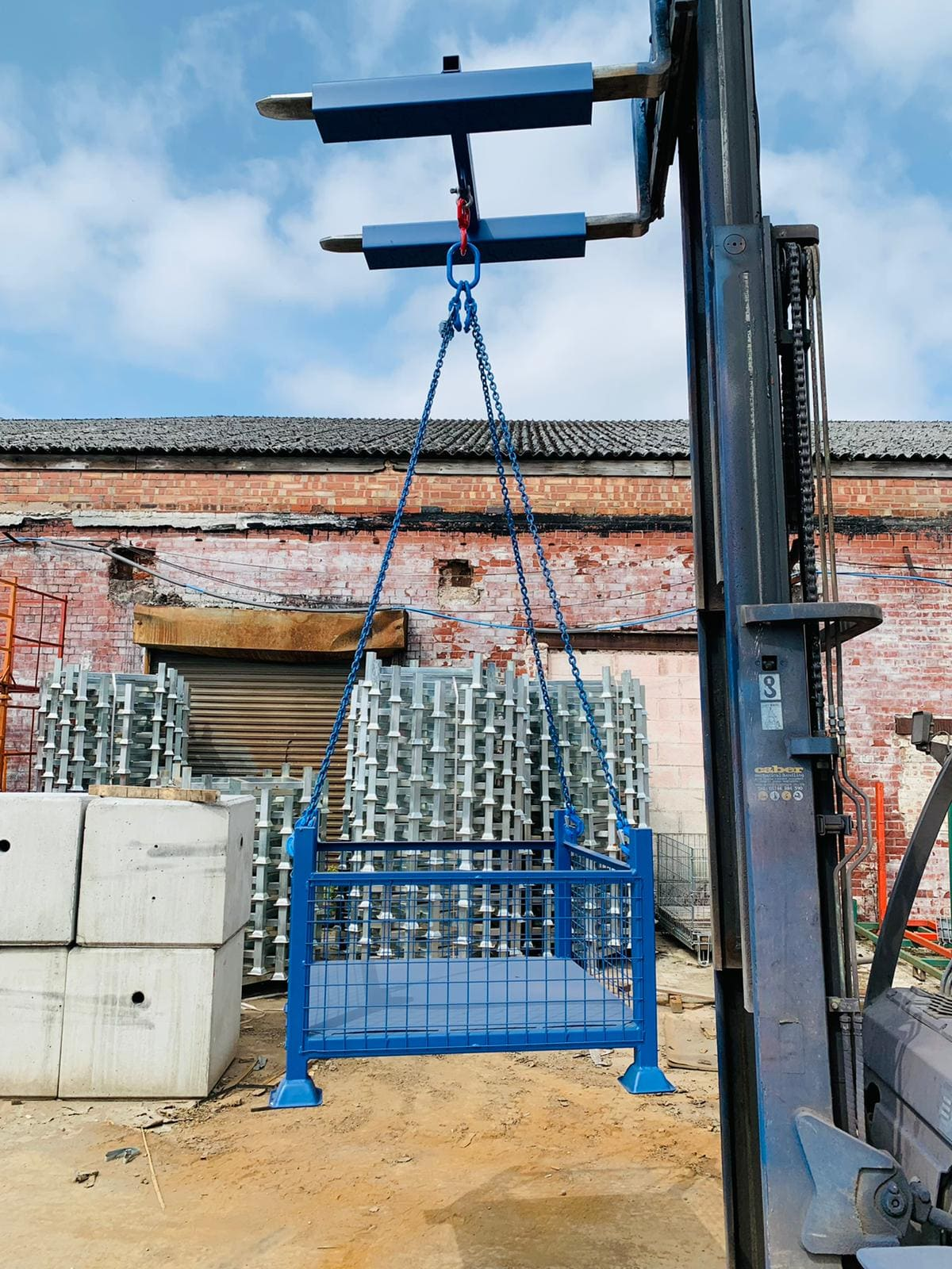 Image of mesh pallet cage being lifted by forklift crane
