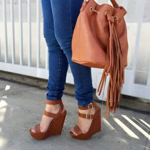 Person holding a baggy brown tote bag while wearing blue jeans and brown open toe wedge sandal heels in size 11, 12, 13, 14, and 15