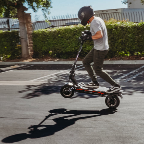Man riding Dualtron Storm electric scooter, front wheel off the pavement