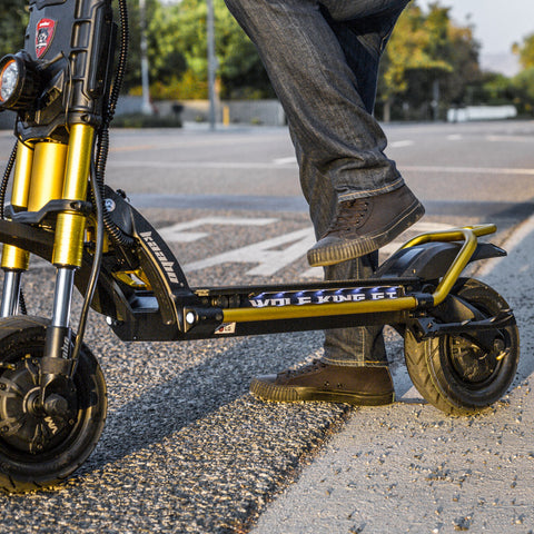 Person stepping onto deck of Wolf King GT electric scooter, cropped view