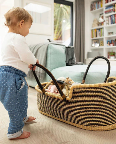 toddler playing with hand woven moses basket bosie baby basket newborns toy storage traditional