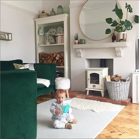 baby on stylish grey padded playmat memory foam with green sofa, plants and fireplace Home decorating interiors inspiration