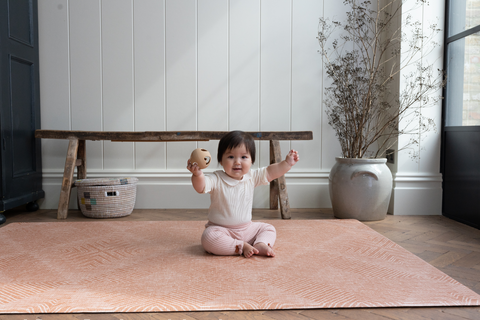 Little girl sitting on a luxury Totter + Tumble playmat